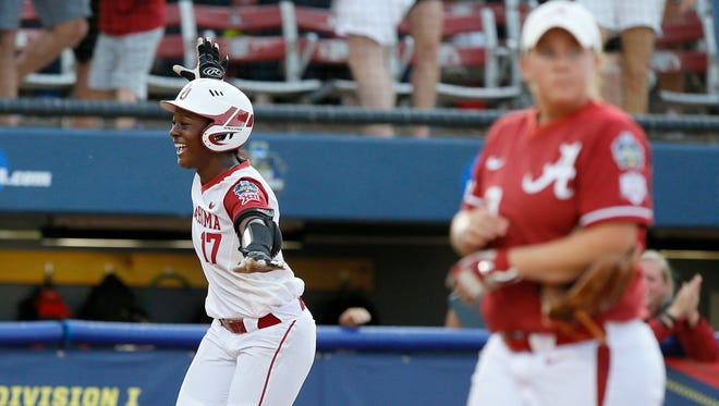 Oklahoma's Shay Knighten, left, runs home after hitting a three-run home run to win in the eighth inning of a college softball game against Alabama in Oklahoma City, Friday, June 3, 2016.