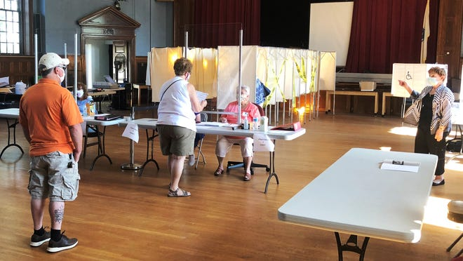 Poll workers at Town Hall said voters had adusted well to the COVID-19 precautions.