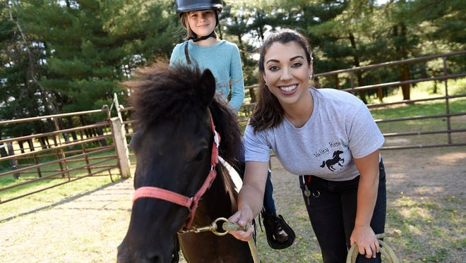 Kalina Gipe, owner of Happy Hooves, LLC, Greencastle, prepares to give Lily Lewis, 9, a ride on her horse, Gilligan, at a site in Clear Spring, Maryland.