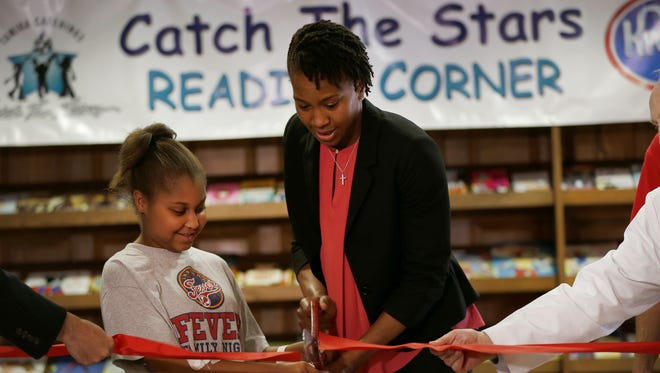 Tamika Catchings, along with the Catch the Stars Foundation, and Riley patient Riann Collier, 12, cut the tap during the unveiling of the new basketball-themed reading corner to the Edward A. Block Family Library at Riley at IU Health. Collier attends every home Fever game with her aunt Velma Coles.