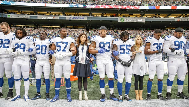 Carlie Irsay-Gordon and Casey Foyt, daughters of Indianapolis Colts owner Jim Irsay, lock arms with Colts players during the national anthem before the Seattle Seahawks game at CenturyLink Field in Seattle on Sunday, Oct. 1, 2017.