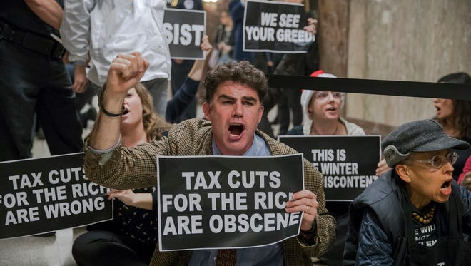 Protesters shout their disapproval of the Republican tax bill outside the Senate Budget Committee hearing room on Capitol Hill in Washington, Tuesday, Nov. 28, 2017. (AP Photo/J. Scott Applewhite)