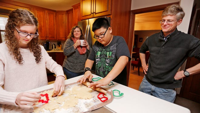Josh and Linda Prokopy look on as children Annabel, 13, and David, 10, use cookie cutters to make Christmas cookies Friday, December 22, 2017, in their West Lafayette home. The cookies will be served up when the family hosts foreign students from Purdue for a holiday meal.