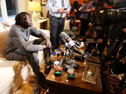 Kentucky's Wenyen Gabriel, left, answers questions from the media after the basketball team watched the NCAA Tournament selection show at the home of head coach John Calipari Sunday, March 11, 2018, in Lexington, Ky. (AP Photo/James Crisp)