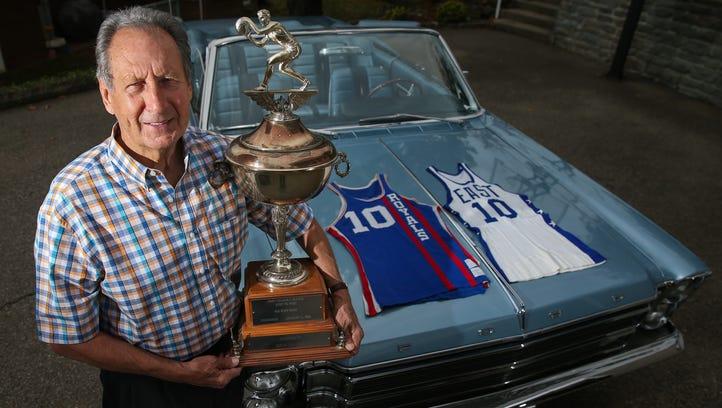 Adrian Smith holds the 1966 NBA All-Star Game Most Valuable Player trophy at his home in Anderson Township with the car he won after receiving the award.