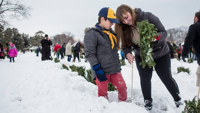Heather Kraft, of Marysville, puts up a wreath with her son, Nathaniel, 7, from Boy Scout Troop 201 at St. Clair County Allied Veterans Cemetery in Port Huron.