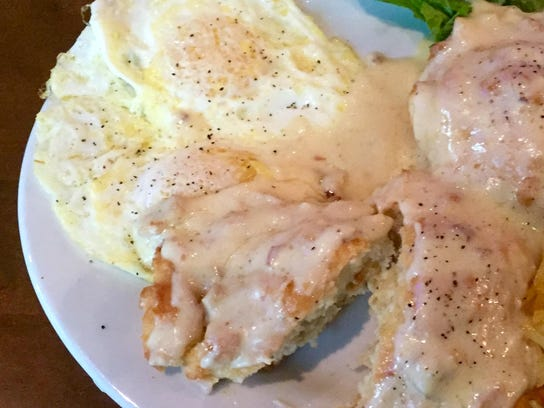 Eggs over-easy and a biscuit swaddled in sausage and
