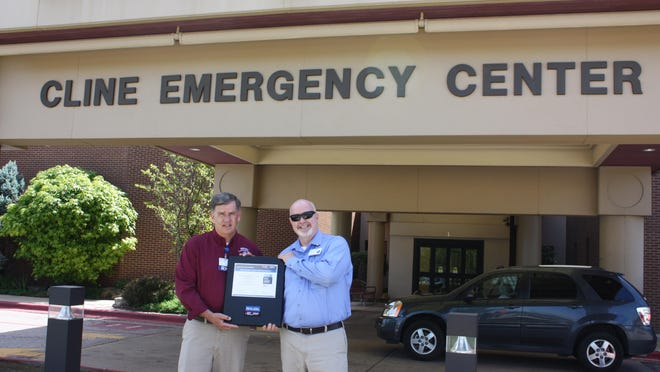 Gerald Cantrell, left, director of ambulance services, and Christopher Fry hold up the 2015 Mission: Lifeline EMS Silver Level Recognition Award that Baxter Regional Medical Center received in May for accomplishing certain standards of care.