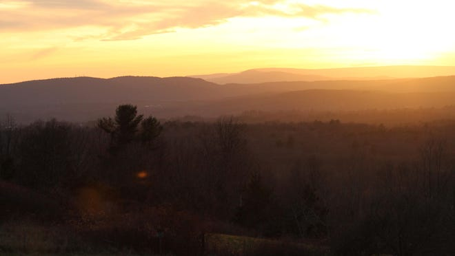 The sun sets over the Catskills, as seen from Burger Hill in Rhinebeck.