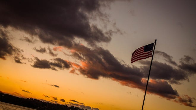 At dusk, an American flag waves on the shore of the Hudson River in Rhinecliff.