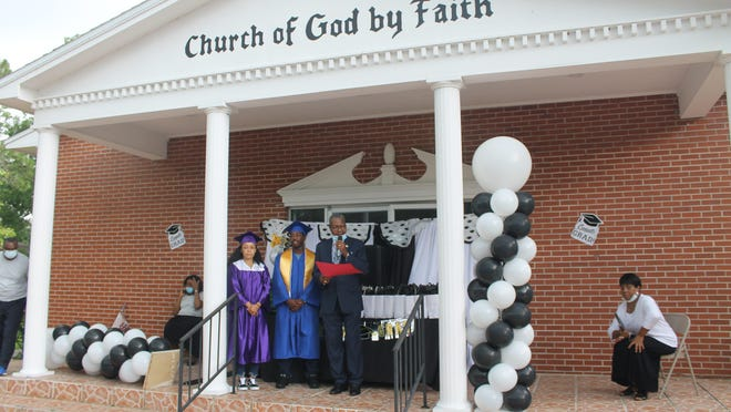 Church of God By Faith located at 735 SE 15th St. hosted a drive-thru graduation celebration on Sunday afternoon to honor 45 youth for completing the school year and two high school graduates. Standing from left are 2020 graduates Gabrielle Rembert of GHS, Tyresse Sanford of the Professional Academies Magnet at Loften High School and Elder Erta C. Livingston Jr., Ph.D., pastor of the church.