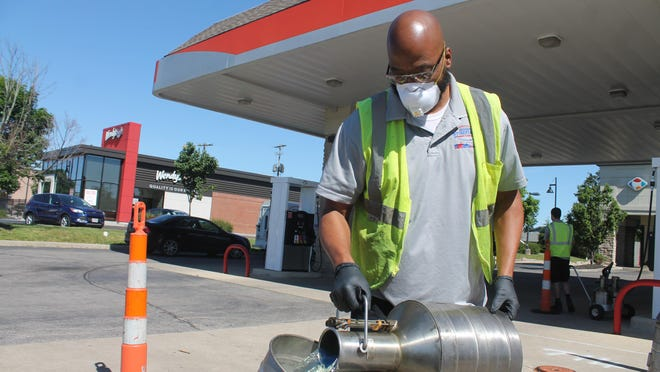 Derrick Bradley, an employee of the Franklin County auditor's office's weights and measures division, pours gasoline from a measuring tank back into the main fuel tank after checking a Stringtown Road gas station pump's accuracy.