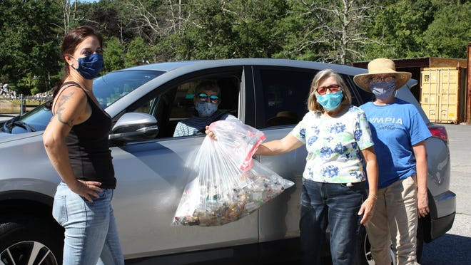 """Longtime Thompson resident Cynthia Antos (pictured in her vehicle) drops off a bag of 50-milliliter liquor bottles collected from her regular walking route in the area of Baker Road. A bottle drive centered around the so-called """"nips"""" ended Saturday at the town highway garage with a total of almost 50,000 little containers collected. From left to right are organizer and town planner Tyra Penn-Gesek, volunteer Jo Ann Hall and Thompson Together president Beth Goldsmith."""