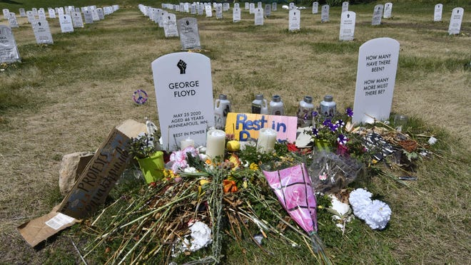 A memorial is set up near a mock tombstone for George Floyd at a symbolic cemetery in Minneapolis on Tuesday.