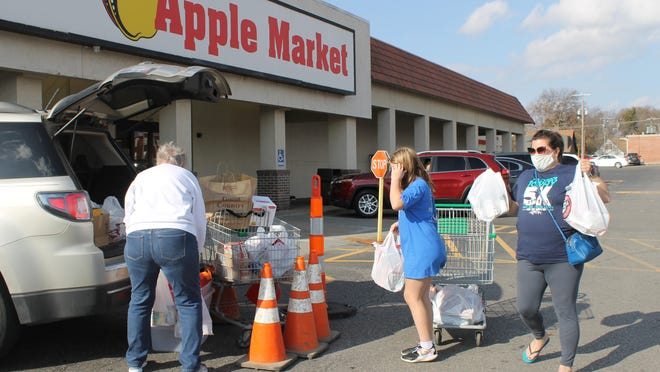 Amy Schell, right, and her daughter Emma help load their donated groceries for the Ronald McDonald House's food pantry drive.