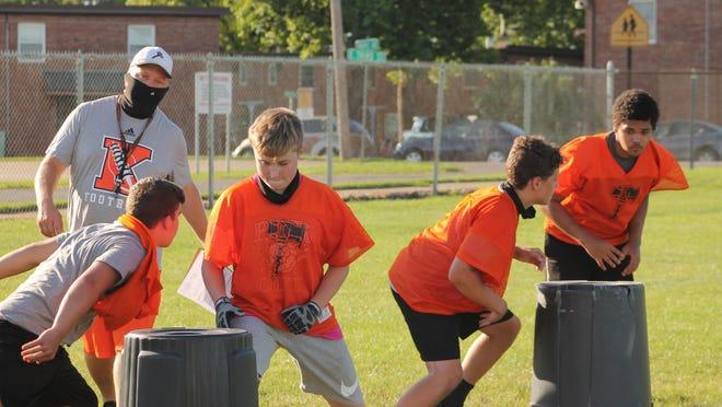 Kewanee High School football coach Brad Swanson conducts drills using barrels on Monday at the school's practice field.