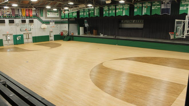 Midway through the process of refurbishing the Wethersfield High School main gym, the floor has been sanded and the 3-point arc stained dark.