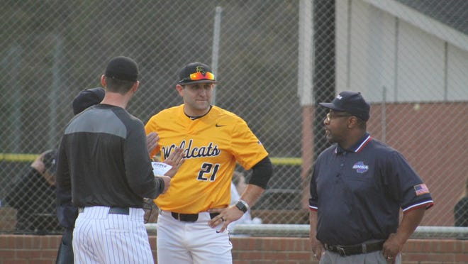 Richmond Hill High School baseball coach Scott Strickland (21) meets with the umpiring crew before a game this season.