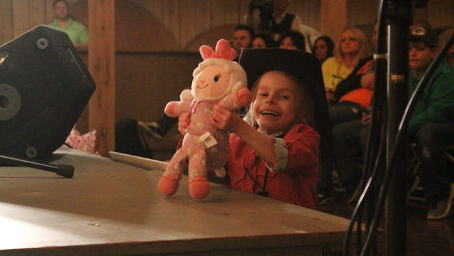 Ashlyn Dale dances next to the stage at her benefit concert Saturday at Snider Farms in Denmark. The 6-year-old has a rare genetic mutation that has left her developmentally delayed, and she loves music.
