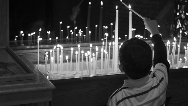 In this photo by MSU student Andrea Raby, a boy lights a votive candle at the Holy Trinity Greek Orthodox Church in Lansing.