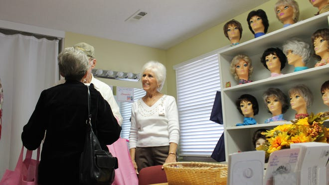 """TJ Hill (right), a volunteer at the Peitz Cancer Support House, showed the """"wig room"""" to visitors on Monday at the Lend-A-Hand Open House. The Lend-A-Hand Campaign supports Baxter Regional Medical Center's four community houses, including Peitz, which offers wigs, at no charge, for cancer patients."""