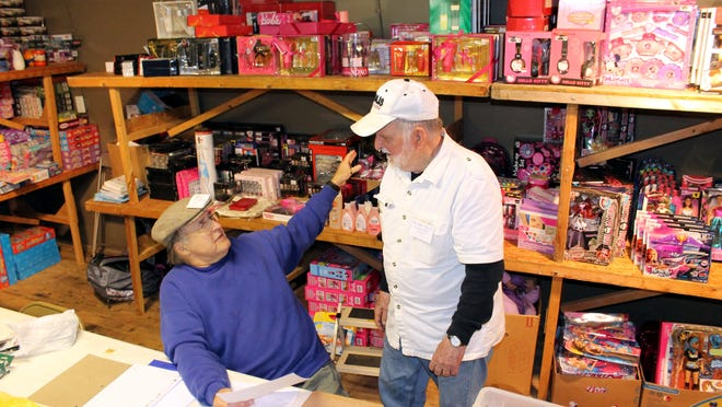 Volunteers Kenn Mochel (left) and Cliff Dubrawsky are shown in the toy room of the Wish Center Tuesday, where they were helping prepare gifts for children.