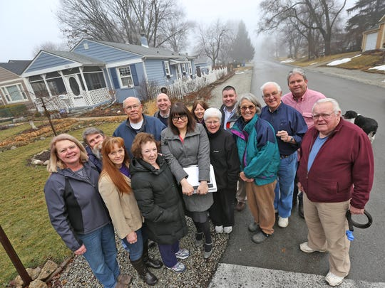 """Members of the North Kessler Park Neighborhood Committee posed on Brouse Avenue on Wednesday, March 11, 2015. Meijer plans to build a supercenter nearby, on the corner of Keystone Avenue and 56th Street. """"People think we're fighting Meijer, but we're not,"""" says Kassandra Green (center, with papers), president of the committee. """"The development could be good if they're willing to work with the community."""""""