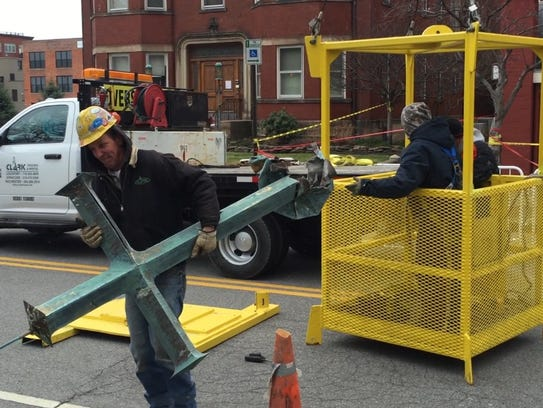 A worker from Spring Sheet Metal and Roofing, of Rochester,