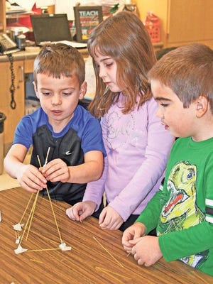 Kindergartners Dalton Sherman, McKenna Trimpe and Jon Stanek collaborate during the Science Month Marshmallow Challenge. Classes were divided into teams that were given 18 minutes to create the tallest tower made from uncooked spaghetti and a marshmallow. Props included a limited amount of string and tape.