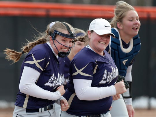 Appleton North High School's Marissa Mullen, left, Sara Allison and Lydia Krueger, right, celebrate their victory against Kaukauna High School during their softball game Tuesday, April 10, 2018, in Kaukauna, Wis. 