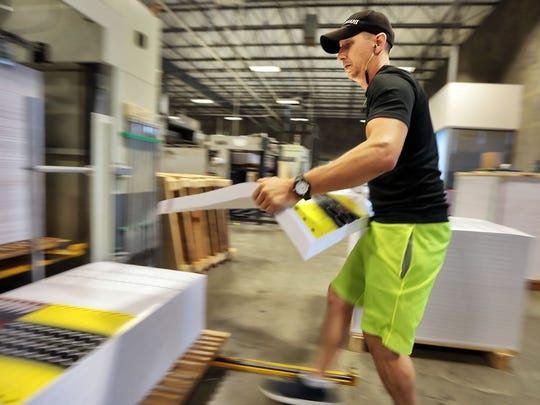 Jon Dauch prints stacks of eclipse glasses as workers at Bartlett-based American Paper Optics work to complete orders for the glasses in advance of the full eclipse next week. The company is making 550,000 solar eclipse glasses daily now, having already sold 45 million pairs.