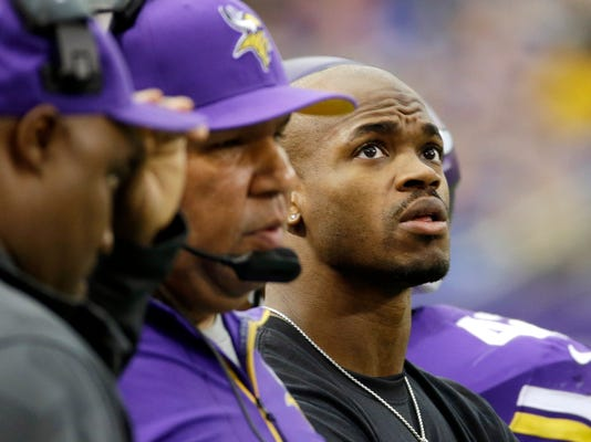 FILE - In this Dec. 29, 2013, file photo, injured Minnesota Vikings running back Adrian Peterson, right, stands on the sidelines during the first half of an NFL football game against the Detroit Lions in Minneapolis. The star running back sure isn't ready to declare himself past his prime, but he did admit he can see the purpose of carrying the ball a little less for the Vikings this season. (AP Photo/Ann Heisenfelt, File)