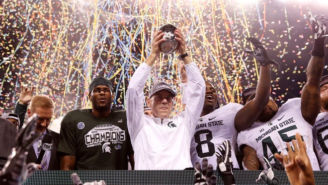 MSU coach Mark Dantonio celebrates with his team after defeating the Iowa Hawkeyes in the Big Ten Championship Game on Dec. 5 at Lucas Oil Stadium.