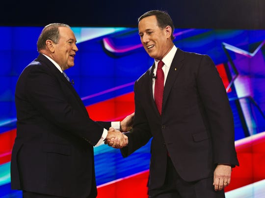 Mike Huckabee shakes hands with Rick Santorum prior to the undercard debate on Dec. 15, 2015.