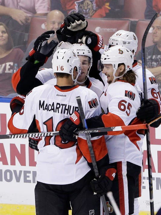 Ottawa Senators left wing Clarke MacArthur (16) is congratulated by teammates after he scored a goal during the second period of an NHL hockey game against the Florida Panthers, Monday, Oct. 13, 2014 in Sunrise, Fla. (AP Photo/Wilfredo Lee)