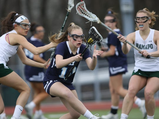 Caroline McKee, of IHA, tries to control the ball between the Ramapo defense, Thursday, April 12, 2018.  IHA went on to win the game, 13-4.