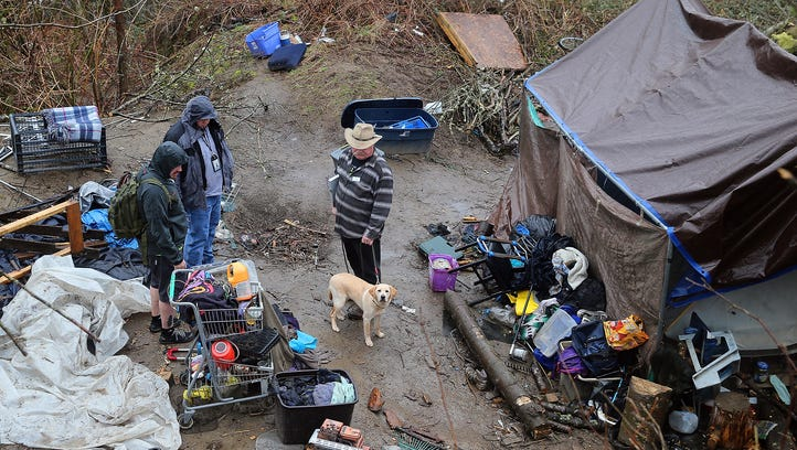Joe Summers, center with his dog Missy, from the Kitsap Rescue Mission visits a homeless encampment in East Bremerton on Friday. On the left is Michael O' Shaughnessy III from the mission, and Richard Bazzell an environmental health specialist from the Kitsap Public Health District.