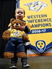 Aiden Brown, 1, holds a teddy bear dressed in Predators