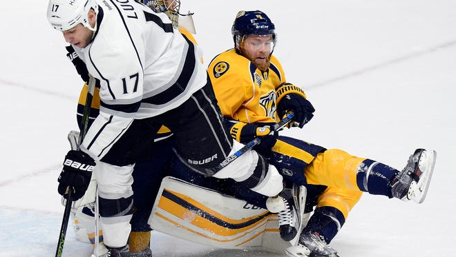 Predators defenseman Ryan Ellis, right, falls over goalie Pekka Rinne (35) after clearing the puck away from Los Angeles Kings left wing Milan Lucic (17) during the first period.