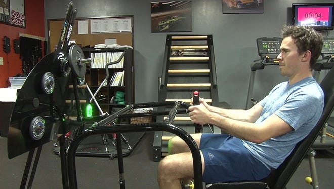 """IndyCar driver Robert Wickens works out at PitFit Training. PItFit is a workout facility that caters specifically to the needs of racing drivers. Wickens is using PitFit's """"Race Trainer,"""" where a driver simulates sitting in the cockpit of a car and cranks a weighted steering wheel to and fro as quickly as possible, trying to keep up with a flashing light. The exercise strengthens the forearms, hands and shoulders."""