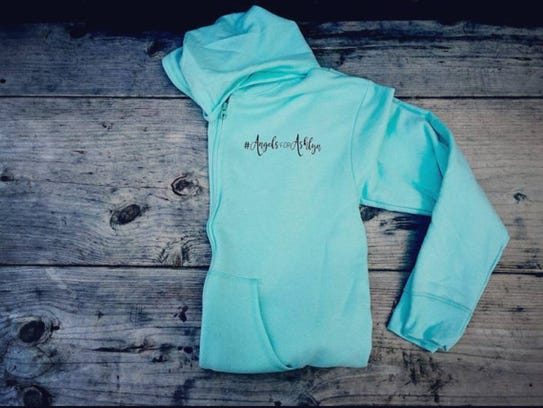 "A sweatshirt reads ""Angels for Ashlyn,"" the name of"