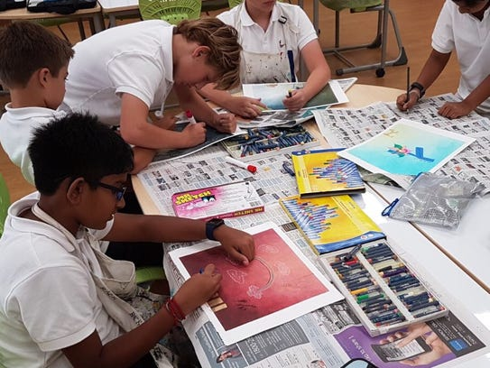 Middle school children in Singapore work on an art