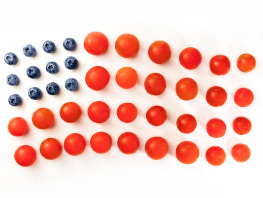 American flag of blueberries and cherry tomatoes on white