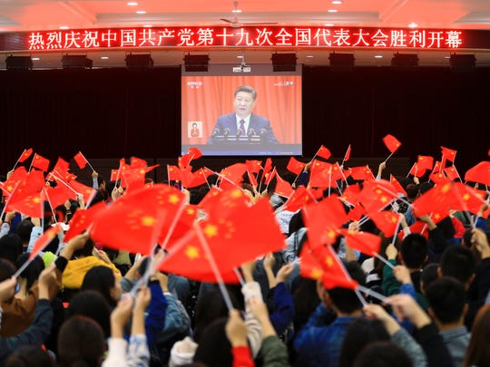 Students wave flags as they watch a speech by Chinese