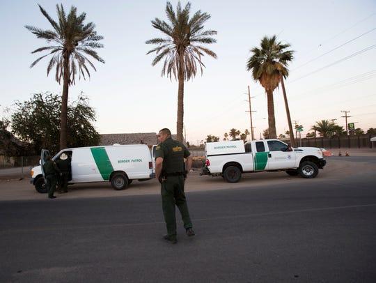Agentes de la aduana y protección fronteriza se preparan para mover inmigrantes indocumentados después de detenerlos por entrar a los Estados Unidos en la frontera internacional en el muro de Calexico/Mexicali el 19 de junio, 2018.