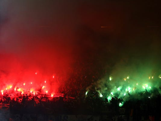 FILE - In this Thursday, Feb. 16, 2017 file photo, St.-Etienne supporters light flares ahead of the Europa League round of 32 first leg soccer match between Manchester United and St.-Etienne at the Old Trafford stadium in Manchester, England. Saint-Etienne must pay 50,000 euros ($54,000) for fans' improper conduct and lighting fireworks at Old Trafford during a 3-0 loss against Manchester United.  (AP Photo/Dave Thompson, File )