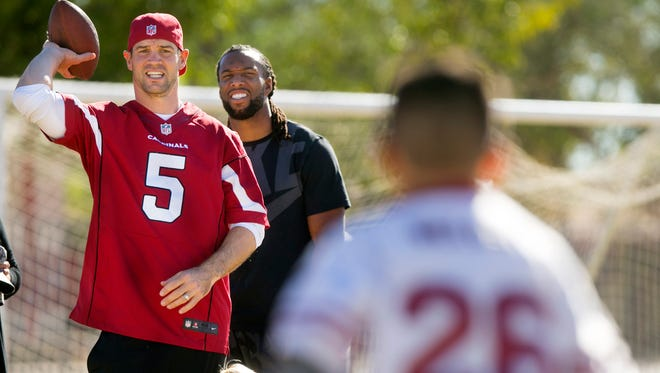Arizona Cardinals quarterback Drew Stanton and wide receiver Larry Fitzgerald run a drill with a student as Stanton's son, Asher Stanton, 2, looks on during the Kids Camp presented by Desert Schools Federal Credit Union at Madison Park Middle School in Phoenix on Tuesday, November 18, 2014.