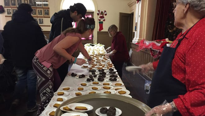 Susan Ellerson, a volunteer at the Bandera Family Christmas Dinner in Binghamton, replenishes the dessert supply.