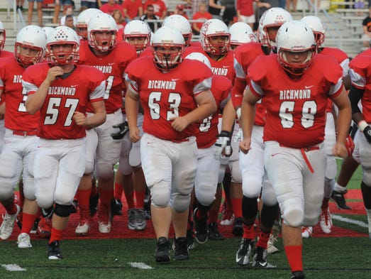 Richmond players head to the sideline for the start of Friday's game against New Palestine at Lyboult Field.