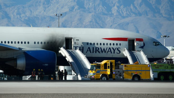 Firefighters stand by a plane that caught fire at McCarran International Airport, Tuesday in Las Vegas. An engine on the British Airways plane caught fire before takeoff, forcing passengers to escape on emergency slides.
